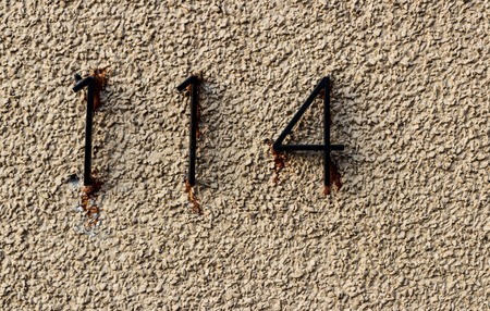 Old grungy white rock wall with the numbers 114 hastily glued with runny adhesive