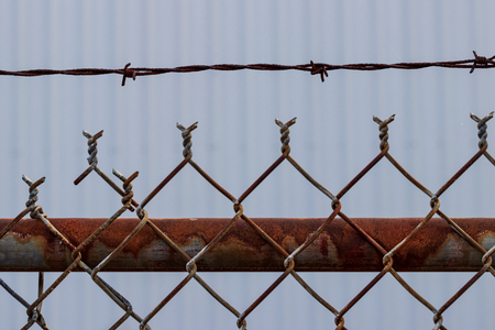 Old rusty chain link barbed wire fence with white wall Stock Photo