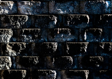 Aged worn grungy cement block wall with dirt and moss showing angled light Stock Photo