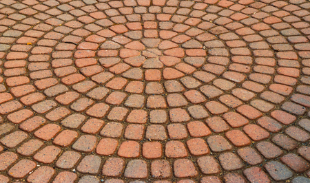 Red circular paved bricks with dirty moss and worn age Stock Photo