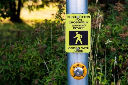 Crosswalk button mechanism on a steel post with a bush