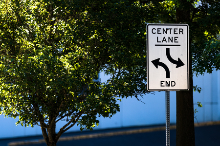 Center lane ends sign with trees, road, and a warehouse in the background