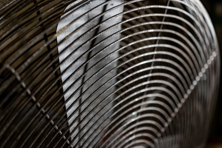 Dirty worn old rusty electric industrial fan close up