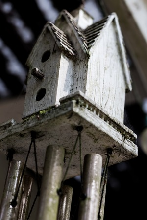 Abstract bird house windchime dirty and weathered with moss Stock Photo