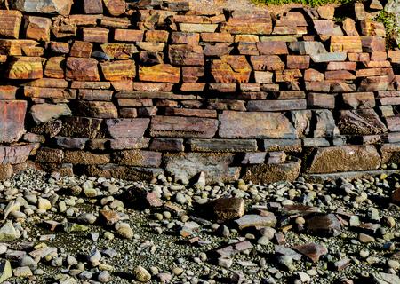 Stacked iron ore stone wall along a rocky beach shoreline Stock Photo