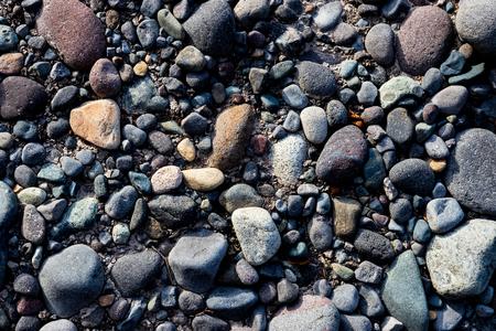 River rocks on a silty muddy bank shore Stock Photo