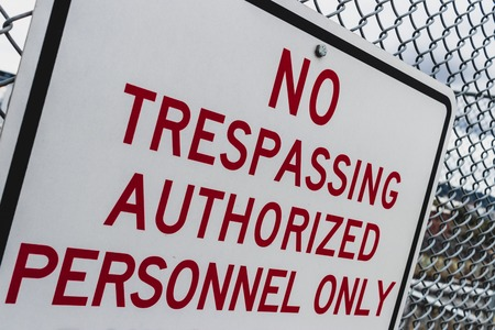 Abstract angle no trespassing authorized personnel sign on fence Stock Photo