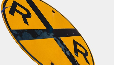 Abstract dirty dingy railroad crossing sign close up with a white sky Stock Photo