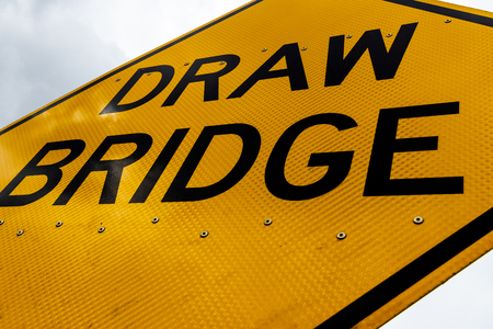 Abstract dirty dingy draw bridge sign close up with a white sky