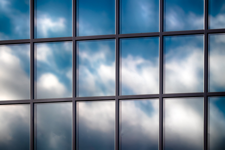 Abstract skyscraper glass window with clouds in reflection and blue sky