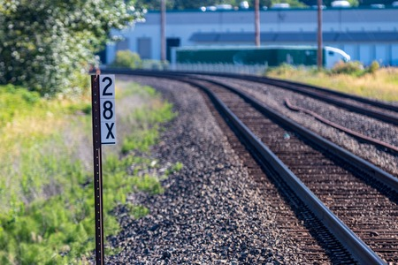 Railroad tracks and sign with building in the distance in daylight Stock Photo