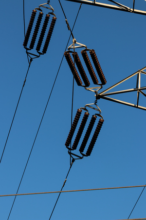 Power line insulators on a blue sky in daylight Stock Photo