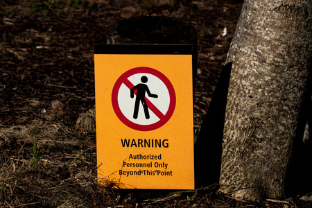 Warning authorized personnel sign on the ground next to tree Stock Photo