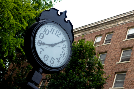 Outdoor clock in front of a brick wall and trees Stock Photo