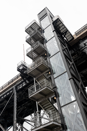 Old external elevator and steel stairway in daylight