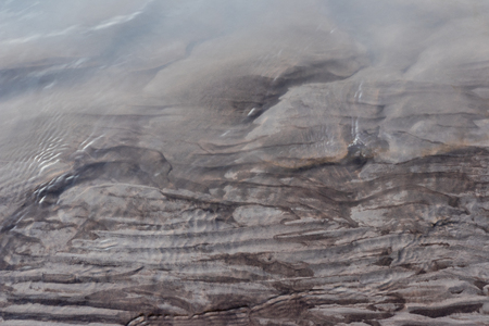 Glacial riverbank shore with wet black silt sand mud water channels