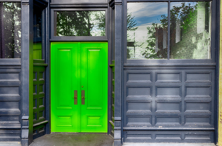 Antique building double doors with windows and faded paint Stock Photo