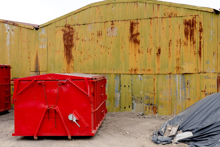 Abandoned old rusty warehouse building with bright red bin
