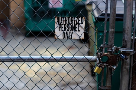 Authorized personnel sign on a chain link fence with bin in the background