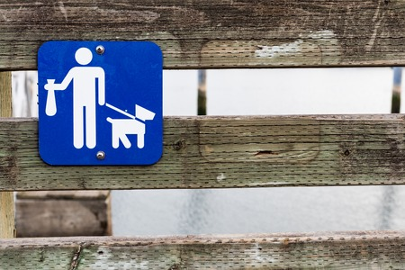 Poop scoop sign on a wooden rail fence in daylight Banque d'images - 123711622