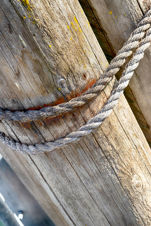 Abstract mooring rope close up on a wooden pylon