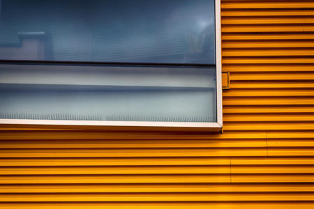Abstract yellow modern building exterior with glass window in daylight Stock Photo