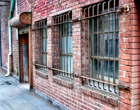 Perspective old brick building with steel bars covering the windows Stock Photo
