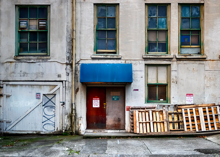 Old building wall with broken windows and doors in daylight Stock Photo