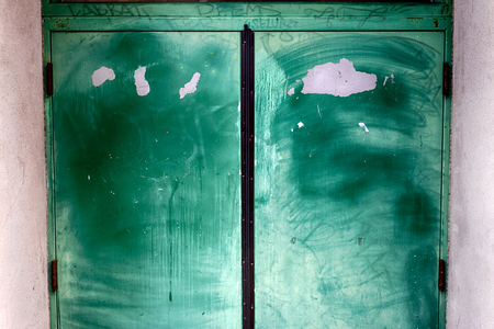 Old worn chipped faded painted building doors in daylight Stock Photo