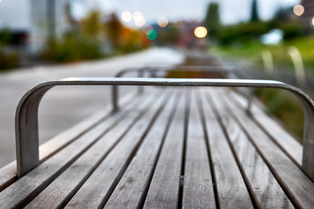 City park bench with buildings and shallow depth of field Imagens - 124764758