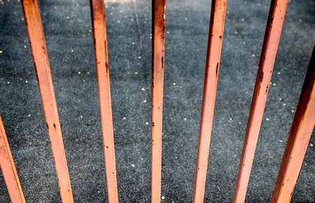 Abstract rusty fence looking over concrete city walkway
