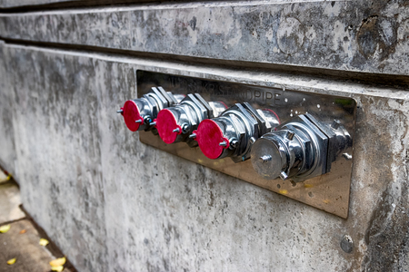 Fire hose nozzles on a building wall in daylight