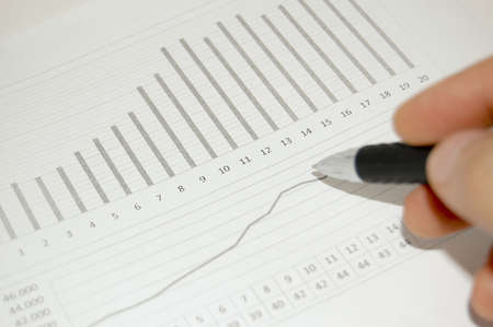 Financial graph with a hand over with a pen Stock Photo - 5436320