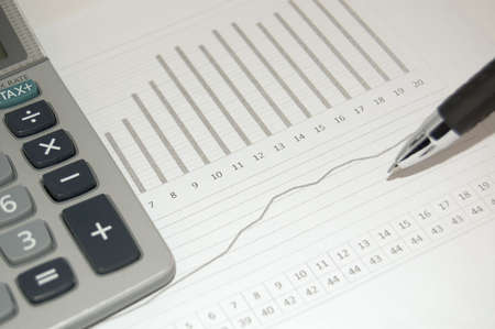 show bill: Financial graph with a pen and calculator on it Stock Photo