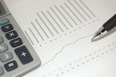 show bill: Gr�fico financiera con un l�piz y una calculadora en ella  Foto de archivo