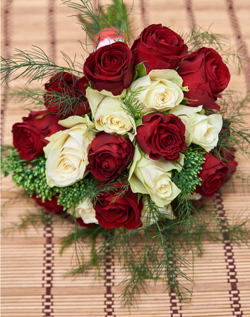 colorful bouquet of white and red roses lying on bege bamboo straw mat, close up
