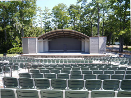 An empty outdoor amphitheatre on a bright day with a lake in the background
