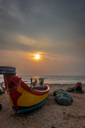 Fishermen boat on the sea shore with rising sun and fishing nets. Archivio Fotografico