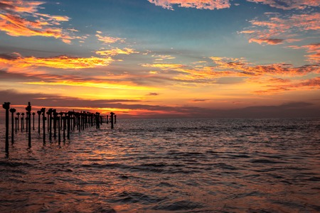 Orange cloud sunset view above sea surface and iron pols at alleppey beach India. cloud image in sun orange rays.