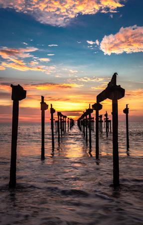 sunset Orange Sky view on the sea water horizon through iron pols taken from low angle at evening Stock fotó