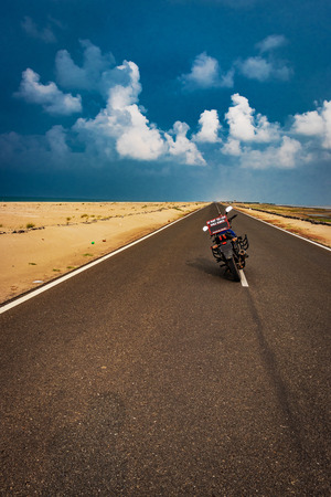 Motorcycle standing on road with life message and left space for you to write something about your experience.