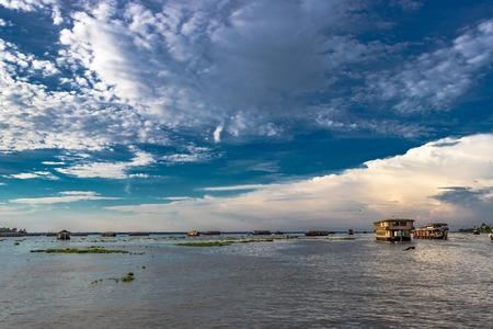 Amazing sky view above backwater of alleppey kerala india with white cloud, blue sky and houseboats. Stock Photo