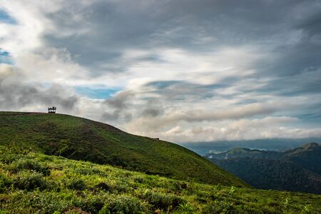 Cloud layers on mountain horizon with green grass image is showing the amazing beauty and art of nature. This image is taken at karnataka india from hilltop.