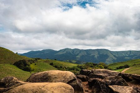 mountain with green grass and beautiful sky image is showing the amazing beauty and art of nature. This image is taken at karnataka india from hilltop. Stock Photo