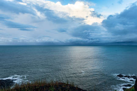 sea horizon view with dramatic cloud from mountain top image is taken at gokarna karnataka india. it is showing the pristine beauty of gokarna beach from hill top.