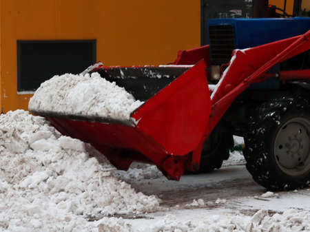 red tractor cleans the snow