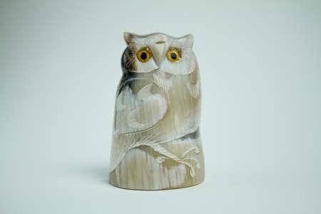 Yak Tusk Owl Figurine on white background, isolated. Stock Photo