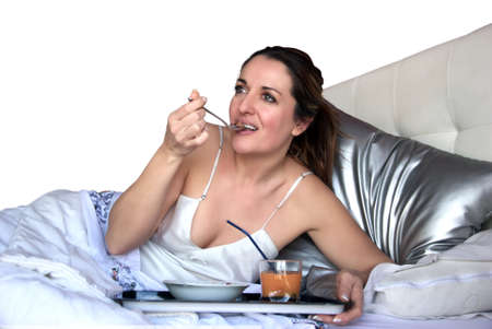woman sitting in bed eating breakfast photo