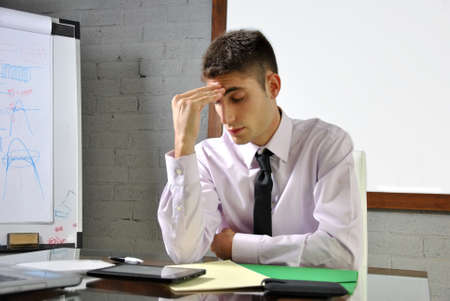 businessman with headache sitting in his office