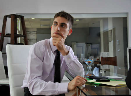 businessman sitting in his office looking at his work Stock Photo
